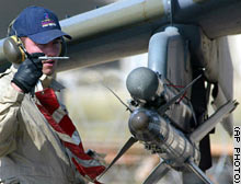 A Royal Air Force ground crewman pulls the safety pin from a Sidewinder missile as final arming of the aircraft is carried out in Kuwait.